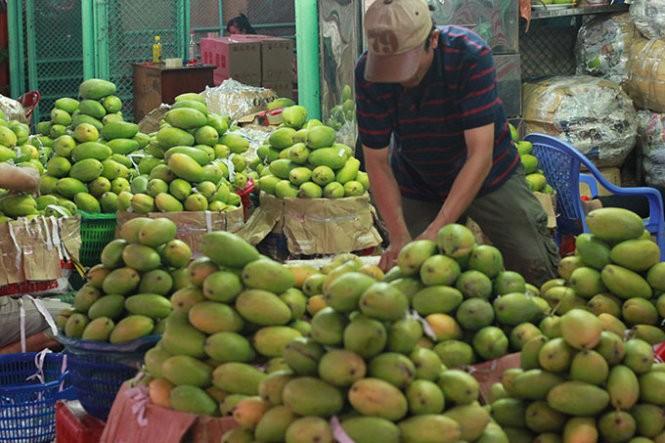 Tiểu thương bày bán trái cây tại chợ đầu mối nông sản Thủ Đức - Ảnh: Lê Sơn