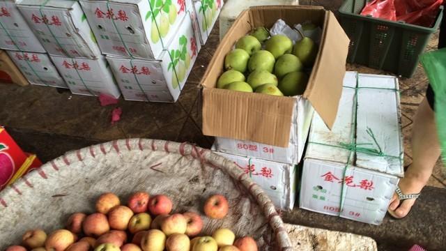 """Chủ các sạp hàng thản nhiên lấy táo, lê từ các thùng Trung Quốc ở phía sau và bán cho khách hàng với """"danh"""" hoa quả miền Nam."""