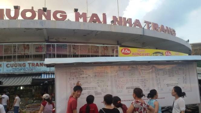 Tiểu thương xem niêm yết về dự án chợ Đầm Nha Trang - Ảnh: Phan Sông Ngân