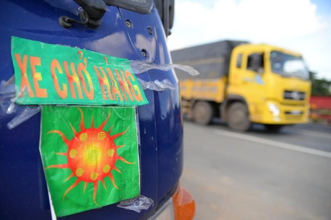 """Xe tải dán logo """"xe chở hàng"""" lưu thông trên quốc lộ 1 đoạn qua địa phận quận Thủ Đức, TP.HCM (ảnh chụp chiều 27-8) - Ảnh: Hữu Khoa"""