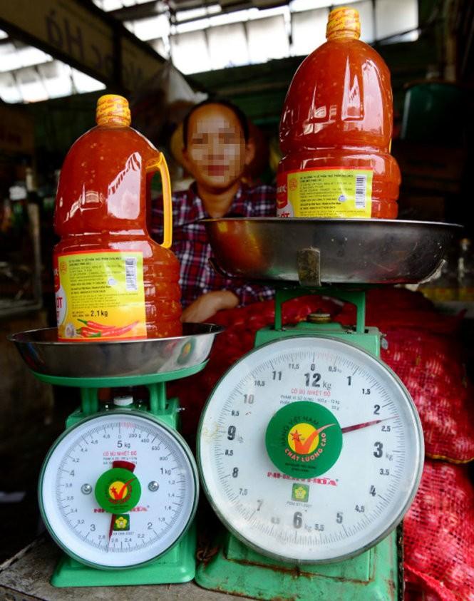 """Cùng cân một khối lượng: cân chuẩn của chợ Bà Chiểu (phải) chỉ số 2,3kg, trong khi đó cân đã được """"độ"""" bên trái lên đến gần 2,7kg - Ảnh: Quang Định"""