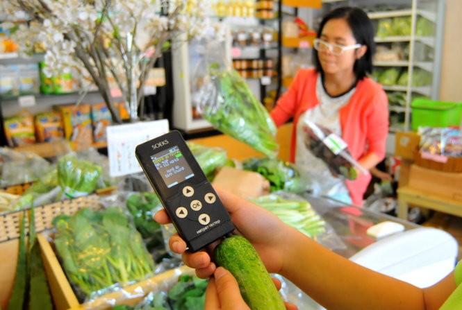 Đo hàm lượng nitrat trong rau củ quả tại một cửa hàng rau sạch ở Q.3, TP.HCM - Ảnh: T.T.D.