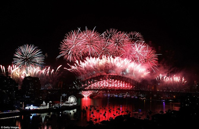 Mép nước của cảng nhìn màu đỏ như bầu trời sáng lên trong một mảng của pháo hoa màu đỏ và trắng, với người vui chơi kinh hoàng nhìn bầu trời