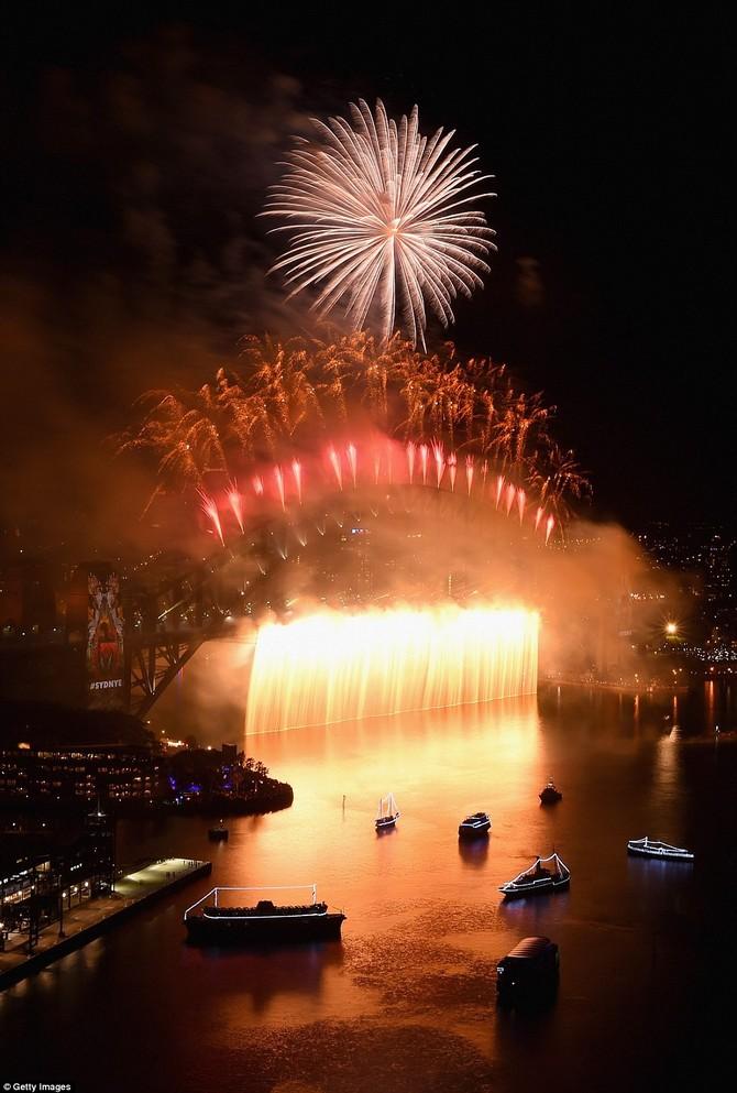 Một dòng pháo hoa vàng trút xuống từ cây cầu để các nước trong khi tia lửa màu đỏ và màu cam bay lên bầu trời
