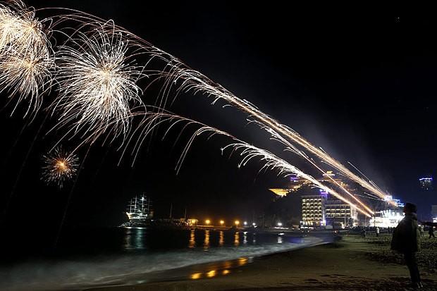 Người ăn mừng với pháo hoa trong một sự kiện của năm mới trên bãi biển ở Jeongdongjin Gangneung, tỉnh Ganwon, Hàn Quốc