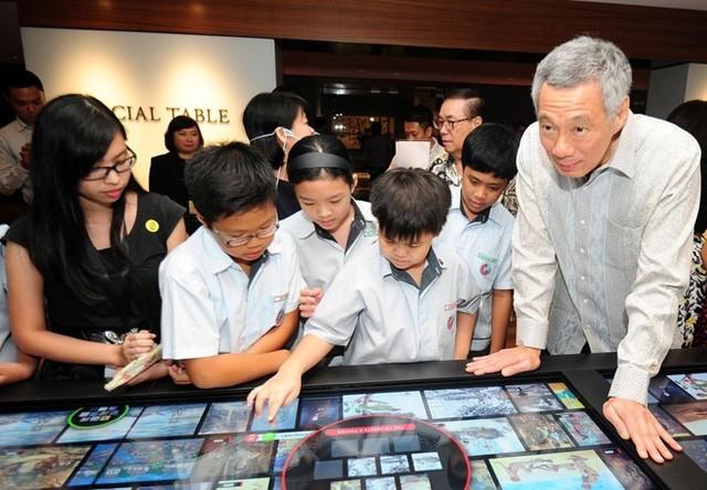 Thủ tướng Singapore Lý Hiển Long, con trai cố thủ tướng Lý Quang Diệu, cùng học sinh tham dự triển lãm quốc gia Singapore. Ảnh: AFP