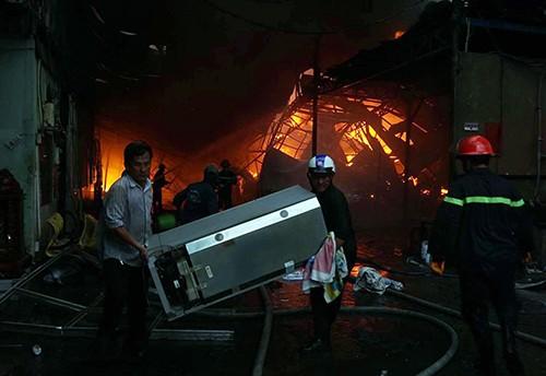 Công nhân di tản tài sản ra khỏi biển lửa. Ảnh: Nguyệt Triều