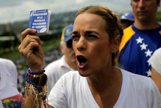 Một người biểu tình với một bản copy Hiến pháp Venezuela trên tay - Ảnh: Reuters.