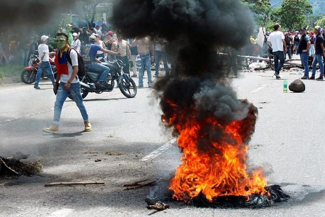 Người biểu tình phản đối ông Maduro ở thành phố San Cristobal của Venezuela. Đã có khoảng 120 người bị thương và gần 150 người bị bắt giữ trong các cuộc biểu tình ở Venezuela ngày 26/10 - Ảnh: Reuters.