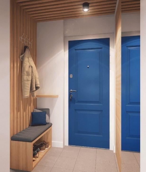 Hành lang nhỏ dẫn vào nhà được bố trí ghế ngồi, kệ để giày và móc treo quần áo. Phía đối diện là một chiếc gương lớn giúp nhân đôi diện tích lối vào nhà.
