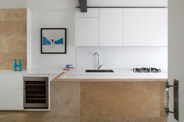 Phòng bếp trắng tinh từ trên xuống dưới nhưng không tạo cảm giác lạnh lẽo mà còn ấm áp nhờ sàn nhà, bức tường và phần kệ bếp được ốp gạch mày nâu.