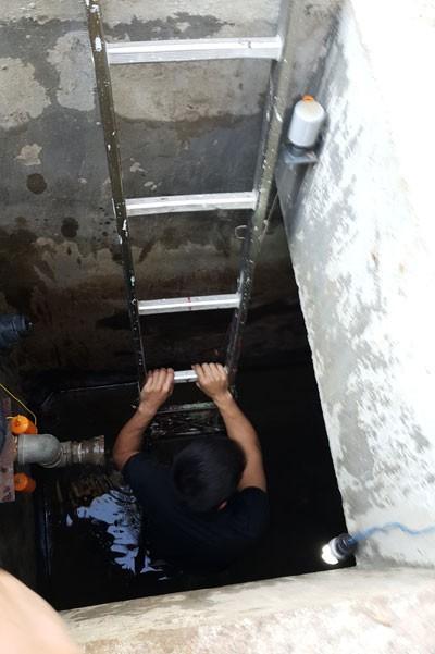 Người dân phải chui xuống bể ngầm để vét từng xô nước. Ảnh: T.Tâm.