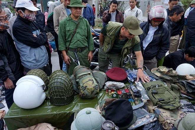 """3. Chợ """"súng đạn"""" ở Hà Nội Chợ phiên đồ cũ này mới hình thành chừng 2 tháng họp vào những ngày mồng 5, mồng 10, 15, 20, 25, 30 âm lịch hàng tháng. Ngoài những đồ cổ, đồ cũ đủ loại, những hộp tiếp đạn, vỏ lựu đạn, súng cũ hỏng, quân phục... từ thời chiến tranh chống Mỹ được bày bán khá nhiều. Những sản phẩm ở chợ có giá từ vài nghìn đồng cho đến hàng trăm triệu đồng. Ảnh: Vietnamnet."""