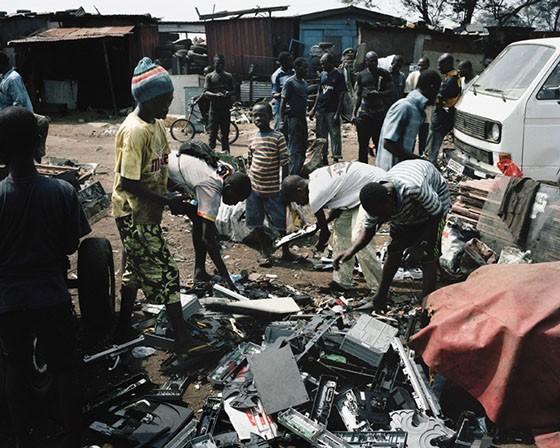 Agbobloshie, Accra, Ghana. Những cậu bé đang thu lượm rác tái chế tại bãi rác Agbobloshie. Những dòng xe tải chở rác thải điện tử từ các thành phố khác hoặc cảng Tema nối thành những hàng dài không dứt. Cảng Tema là cảng biển chính của Ghana, chủ yếu nhận hàng từ Mỹ và châu Âu.