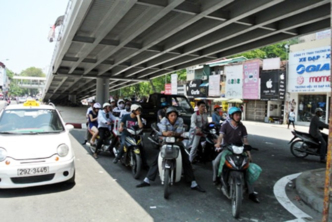 Những người đứng tránh nắng dưới gầm cầu đã làm chật kín làn đường dành cho xe quay đầu ở ngã tư Láng Hạ - Thái Hà.
