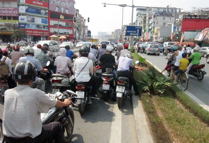 Tại ngã tư Xã Đàn - Đại Cồ Việt, lợi dụng bóng râm được tạo ra từ cầu vượt dành cho người đi bộ qua đường, người dân dừng xe tránh nắng dù cách vạch sơn cả chục mét.