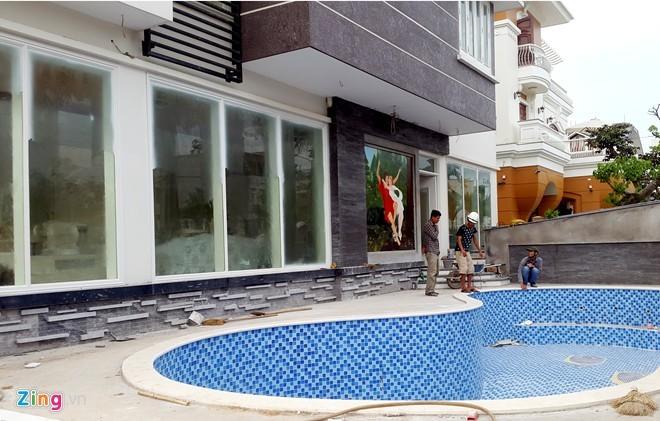 Phía cổng sau được thiết kế theo kiểu biệt thự hiện đại gồm bể bơi, các phòng khách, ngủ được lắp cửa kính hoàn toàn.