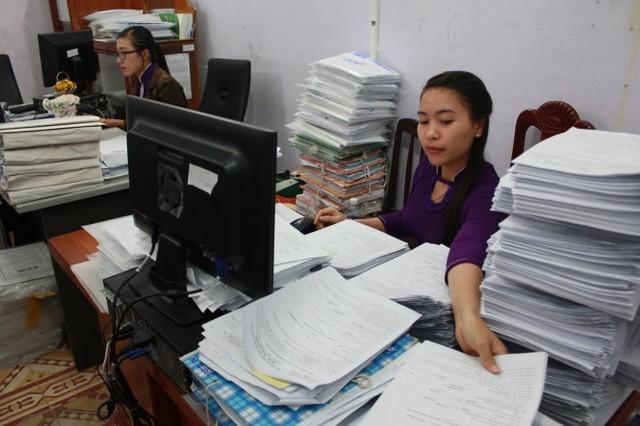 Chi cục Thuế huyện Phú Quốc quá tải với hồ sơ khai thuế nhà đất. Trong ảnh: nhân viên bộ phận chuyên trách hồ sơ thuế nhà đất Chi cục Thuế huyện Phú Quốc với đống hồ sơ cao ngút - Ảnh: Đình Dân