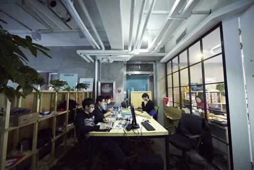Doanh nhân trẻ ngồi làm việc tại chiếc bàn họ đã thuê ở các quán cà phê như 3W doanhnhansaigon