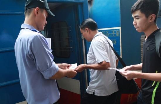 Nhân viên tàu SE5 kiểm tra, hướng dẫn hành khách sử dụng thẻ lên tàu trước giờ khởi hành - Ảnh: T.Phùng