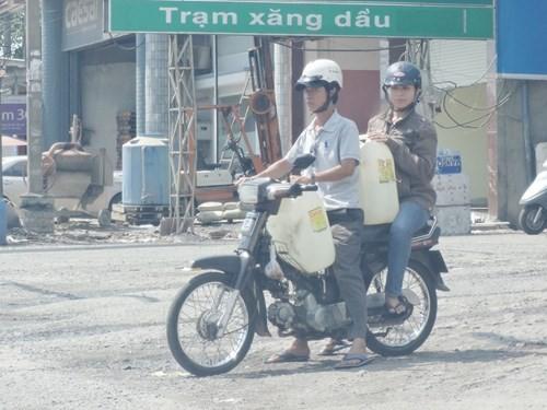Chị Phương (ngồi sau) trong vai người mua bán xăng lẻ đi trinh sát - Ảnh: Sở KH-CN Đồng Nai