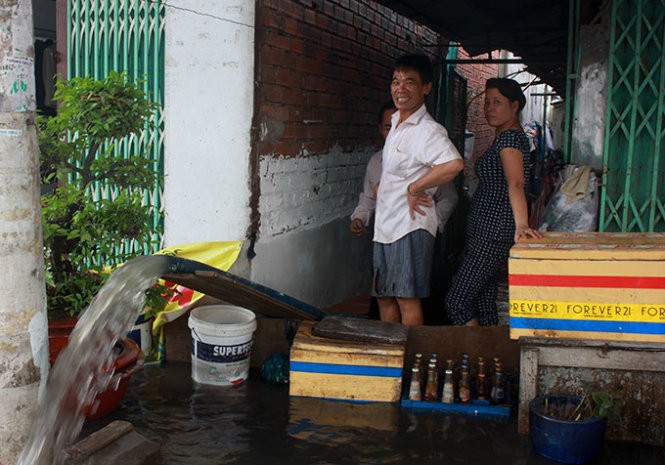 Một hộ dân ở đường Ấp Chiến Lược (Q.Bình Tân, TP.HCM) phải bơm nước từ trong nhà ra ngoài sau cơn mưa ngày 9-9 - Ảnh: ĐỨC PHÚ