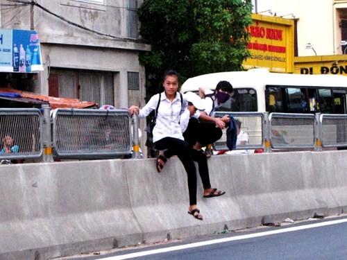 Học sinh vô tư leo qua điểm tháo tấm lưới ở đoạn qua thôn Thanh Khê, xã Thanh Trạch