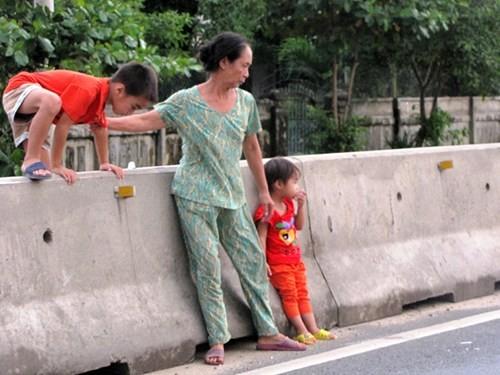 Người lớn vô ý dẫn trẻ em leo qua dải phân cách, em bé trong ảnh sợ khép nép khi xe ô tô liên tục lao qua