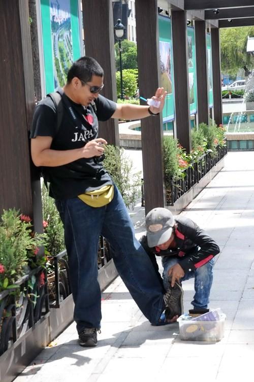Một người đánh giày đang cố lột giày của khách du lịch tại TP.HCM
