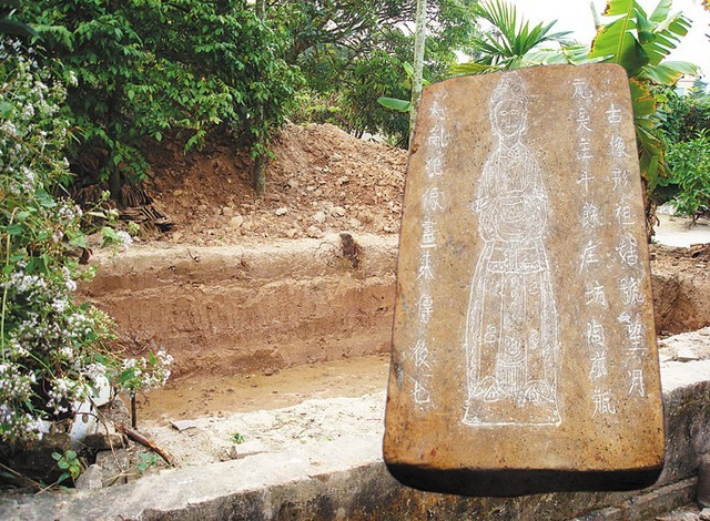 Hố khai quật và viên gạch có khắc hình tượng bà Bùi Thị Hý.