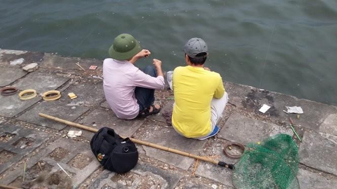 """Hai """"sát thủ"""" đang đánh bắt cá ở khu vực phía sau trường THPT Chu Văn An - Ảnh: Quang Thế"""