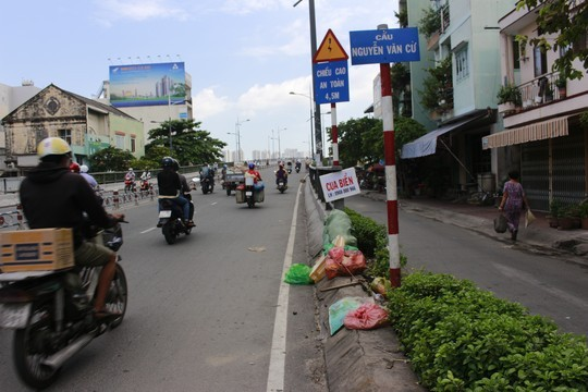 Ngay chân cầu Nguyễn Văn Cừ là bãi rác lớn, bên trên đặt một biển rao bán cua biển của gánh hàng rong trên cầu.