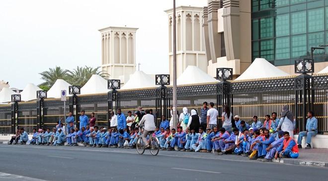 Nhóm công nhân chờ xe buýt để về khu vực sống, bỏ lại phía sau thành phố Dubai hoa lệ trong mắt khách du lịch. Ảnhh: Flickr.