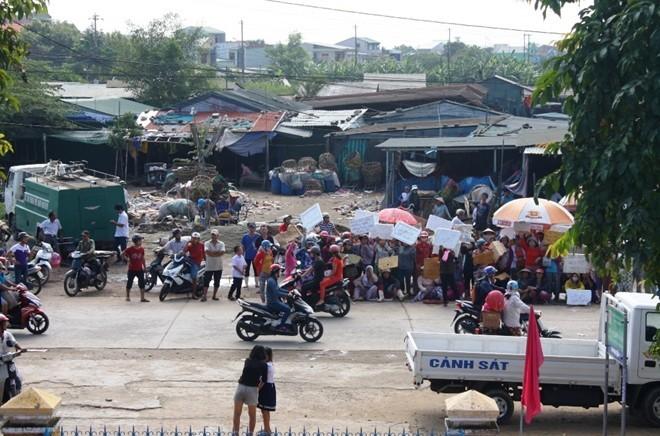 Tiểu thương cố thủ trước cổng chợ tạm. Ảnh: Điền Quang