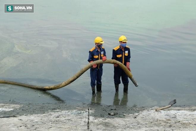 Nhân viên vệ sinh môi trường đặt ống hút nước từ trong hồ thải ra ngoài.