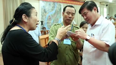 Chủ tịch UBND TP Nguyễn Thành Phong (ngoài cùng bên phải) trao đổi với người dân sau cuộc đối thoại Ảnh: Đào Ngọc Thạch