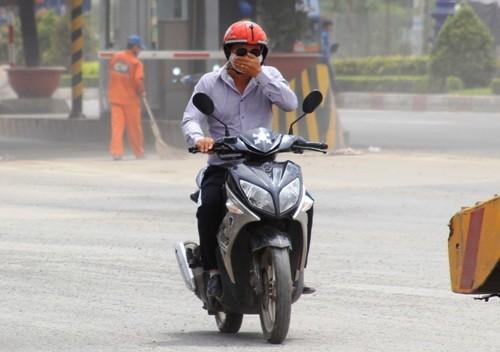 Người đi xe máy dù đeo khẩu trang cũng phải dùng tay bịt mũi để hạn chế bụi bay vào mặt