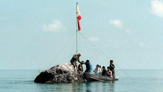 Người Philippines cắm quốc kỳ ở bãi cạn Scarborough, bị Trung Quốc dùng vũ lực chiếm đóng từ năm 2012 Ảnh: Phil Star