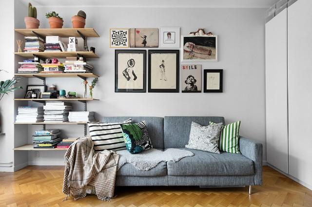 Góc tiếp khách được bố trí đơn giản với ghế sofa dài sát tường. Đây là không gian lý tưởng không chỉ để tiếp khách mà còn là nơi chủ nhà nằm dài thoải mái để gặm nhấm những cuốn sách trên những kệ dài treo trên tường.