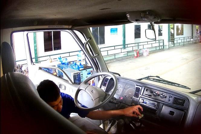 Đăng kiểm viên Trung tâm 50-05V lấy tiền trước khi kiểm định - Ảnh: Gia Minh