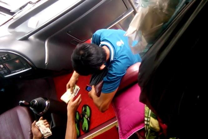 """""""Cò"""" Phước nhận tiền từ lái xe - Ảnh: Gia Minh"""