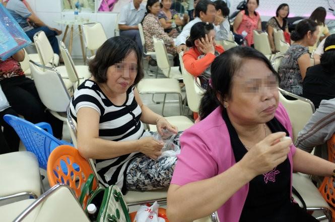 Hai nhà đầu tư ở Vũng Tàu chờ đợi tại Công ty TNHH sản xuất thương mại Kim Mỹ (quận Tân Bình) mong lấy lại được tiền - Ảnh: Hoài Linh