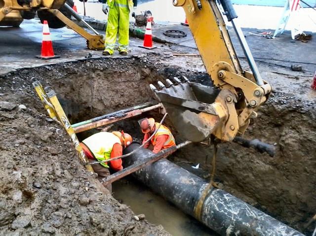 Công nhân sửa chữa đường ống dẫn nước bằng gang bị vỡ ở Oregon, Mỹ.