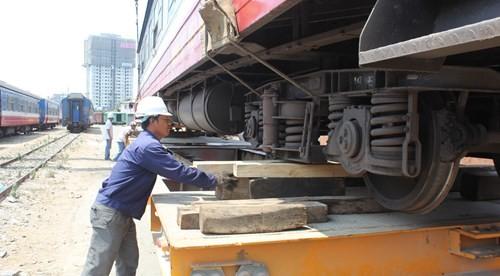 Công nhân dùng gỗ để cố định các toa tàu