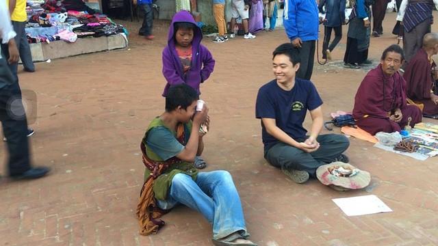 Anh Quỳnh lấy số tiền trong mũ đưa cho một người ăn xin khác. (Ảnh: Nguyễn Ngọc Quỳnh)