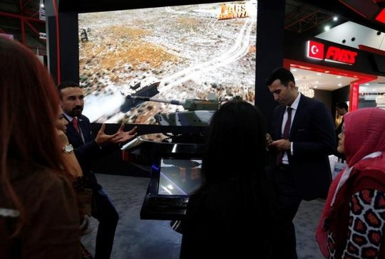 Đại diện của một công ty sản xuất vũ khí Thổ Nhĩ Kỳ giới thiệu xe tăng tại triển lãm. Ảnh: Reuters