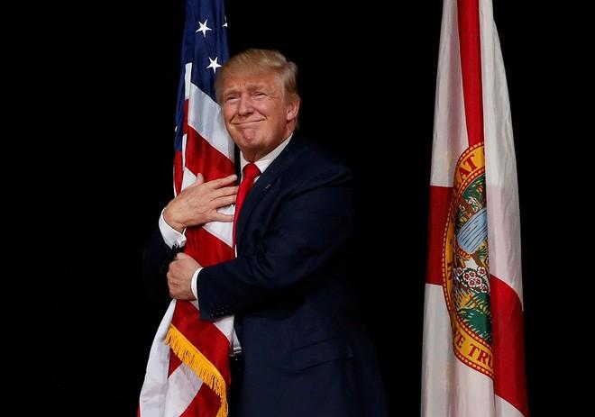 Ông Trump ôm một lá cờ Mỹ khi lên sân khấu vận động tranh cử ở Tampa, Florida hôm 24/10/2016 - Ảnh: Reuters.