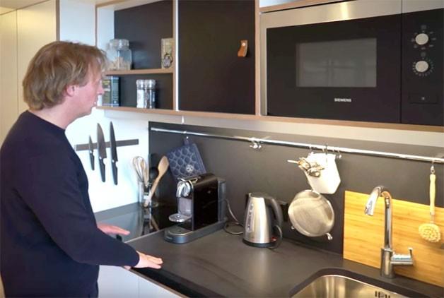 Bếp ăn được thiết kế đặc biệt với tông màu đen nổi bật. Bên trên là tủ kệ mở, nơi đặt lò vi sóng cùng những kệ và móc treo đồ thuận tiện cho người nội trợ. Bên dưới là các ngăn chứa tủ lạnh, máy rửa bát và góc tủ đặt thùng đựng rác.