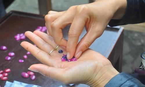 Người phụ nữ tứ tuần cho hay, chủ gian hàng lấy sản phẩm đá đã chế tác sẵn hoặc đá sơ chế thô rồi bày biện trên bàn gỗ theo từng loại.