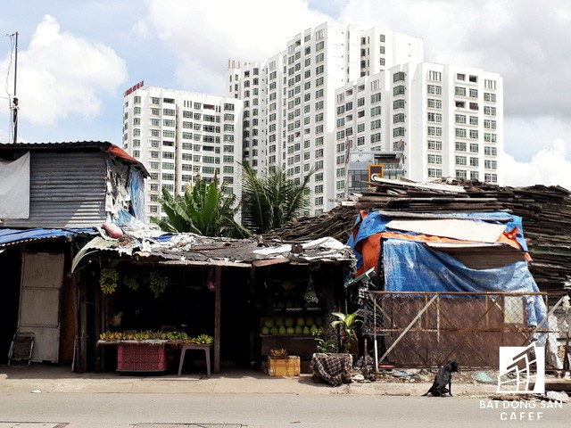 Bên cạnh những tòa nhà chung cư cao tầng là rất nhiều ngôi nhà được che chắn tạm bợ bằng những cây xà cừ và vài ba tấm tôn hoen gỉ.